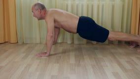 O atleta masculino caucasiano novo em fazer do sportswear empurra levanta em casa Homem do treinamento que exercita a aptidão video estoque
