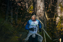 O atleta masculino novo na faixa e nos vidros corre ao longo da fuga de caminhada foto de stock