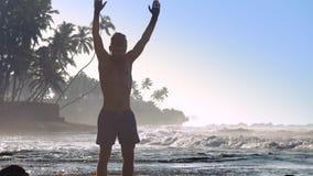 O atleta muscular agita as mãos que fazem o exercício no verão filme