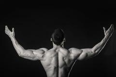 O atleta muscular demonstra seus músculos sob a carga em um fundo escuro foto de stock