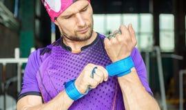 O atleta muscular novo do moderno põe apertos da proteção da palma sobre foto de stock