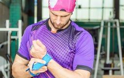 O atleta muscular novo põe apertos da proteção da palma sobre fotos de stock royalty free