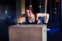 O atleta que fêmea fazer empurra levanta na caixa de madeira Fotos de Stock Royalty Free