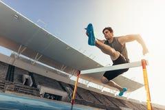 O atleta que salta sobre um obstáculo na pista de atletismo imagens de stock royalty free