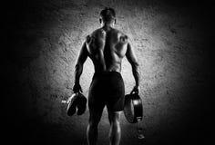 O atleta vai ao gym para treinar Em suas mãos guarda fotografia de stock