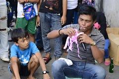 O ator da rua com um grupo de pessoas no quadrado do townl demonstra truques com papel imagens de stock