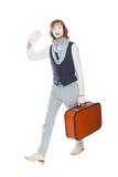 O ator mimica ondas sua mão com mala de viagem alaranjada foto de stock