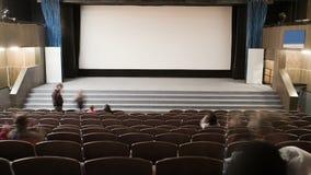 O auditório do cinema está aglomerando-se por povos