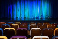 O auditório no teatro Cortina azul esverdeado na fase Cadeiras espectadoras coloridos Projetor do salão da iluminação equipment Imagens de Stock Royalty Free