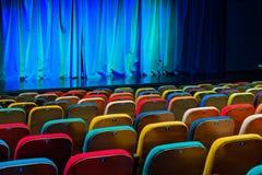 O auditório no teatro Cortina azul esverdeado na fase Cadeiras espectadoras coloridos Projetor do salão da iluminação equipment Foto de Stock Royalty Free