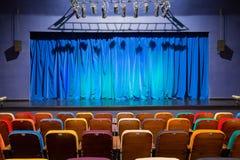 O auditório no teatro Cortina azul esverdeado na fase Cadeiras espectadoras coloridos Projetor do salão da iluminação equipment Imagem de Stock Royalty Free