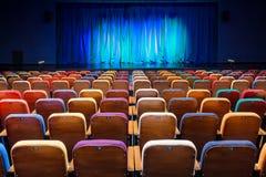 O auditório no teatro Cortina azul esverdeado na fase Cadeiras espectadoras coloridos Projetor do salão da iluminação equipment Foto de Stock