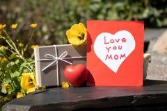 O auto fez o cartão, o coração branco no fundo vermelho, uma caixa de presente e a imagem de stock