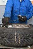 Ar de enchimento do mecânico em um pneumático do carro Foto de Stock Royalty Free