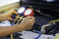 O auto mecânico usa um calibre de pressão no compressor de ar, líquido Foto de Stock