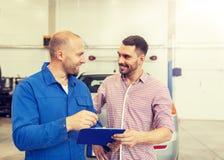 O auto mec?nico com prancheta e o homem no carro compram foto de stock royalty free