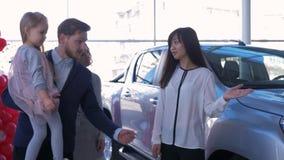 O auto negócio, a família feliz nova com o automóvel das compras da filha e a vendedora asiática dão chaves das mãos em vendas do filme