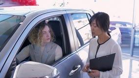 O auto negócio, vendedor asiático do carro da mulher consulta a menina do cliente no carro e cede chaves após a venda bem sucedid video estoque