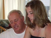O avô e Grandaughter leram o cartão da graduação Fotografia de Stock Royalty Free