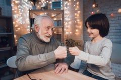 O avô e o neto estão jogando as tesouras de papel da rocha na noite em casa foto de stock