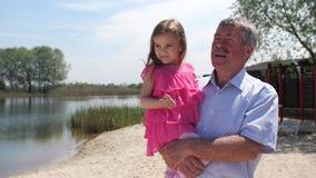 O avô está levando uma neta em seus braços, mostra algo e di-lo Passeio na praia 4K mo lento filme