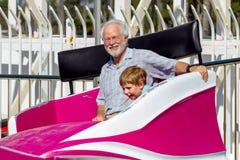 O avô olha a câmera que sorri como ele e sua rotação do neto fotografia de stock royalty free