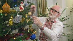 O avô atrativo idoso decora uma árvore de Natal em casa video estoque