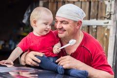 O avô e o bebê que sorriem e olham-se Imagens de Stock Royalty Free