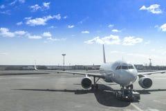 o avião é arrastado pelo aeroporto e pelo embarcadouro do carro no international foto de stock