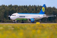 O avião Airbus A320 de linhas aéreas de Usbequistão está aterrando na pista de decolagem Fotografia de Stock Royalty Free