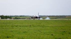 O avião Airbus A319 do passageiro da Aurora está aterrando Fumo de debaixo do chassi atrás dos aviões fotos de stock