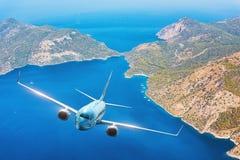 O avião azul está voando sobre ilhas e mar no nascer do sol no verão Imagens de Stock Royalty Free