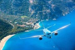 O avião azul está voando sobre ilhas e mar no nascer do sol no verão Foto de Stock