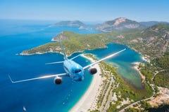 O avião azul está voando sobre ilhas e mar no nascer do sol no verão Imagens de Stock