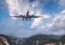 O avião branco grande está voando no céu nebuloso no por do sol Imagens de Stock Royalty Free