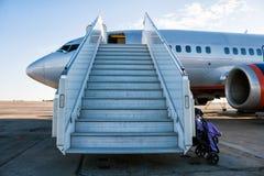 O avião com um embarque do passageiro pisa no avental do aeroporto com um carrinho de criança preparado para o transporte de cria foto de stock royalty free