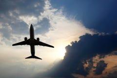 O avião comercial voa em nuvens suculentas para encontrar o sol fotografia de stock