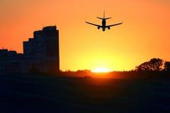 O avião comercial voa no por do sol no fundo do arranha-céus b foto de stock