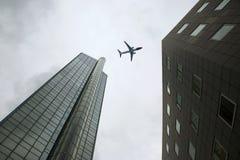 O avião comercial voa sobre arranha-céus foto de stock royalty free