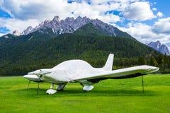 O avião da hélice estacionou no gramado, protegido inteiramente por um b Fotografia de Stock Royalty Free