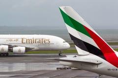 O avião de Airbus A380 das linhas aéreas dos emirados taxis após a cauda de linhas aéreas Boeing dos emirados 777 aviões Fotografia de Stock