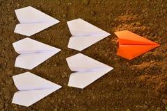 O avião de papel na terra e na laranja é liderança do branco Imagens de Stock Royalty Free