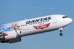 O avião de passageiros de Qantas Boeing 767 com as marcações especiais para promover Disney aplana o filme que descola de Sydney  Fotografia de Stock