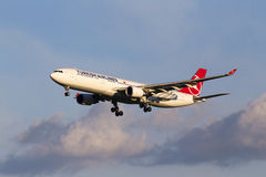 O avião de Turkish Airlines Airbus A330-300 da aterrissagem no por do sol irradia Foto de Stock