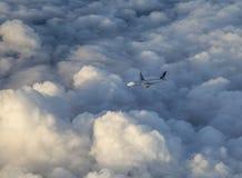 O avião de United Airlines voa nas nuvens escuras com luz solar Fotografia de Stock