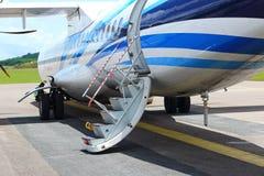 O avião do ATR 72-600 na pista de decolagem do táxi do aeroporto com gramas coloca Imagem de Stock