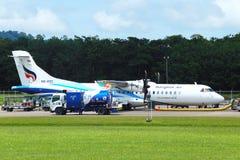 O avião do ATR 72-600 na pista de decolagem do táxi do aeroporto com gramas coloca Fotografia de Stock