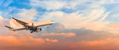 O avião do passageiro é engrenagem da aproximação de aterrissagem liberada, contra nuvens do céu do por do sol, panorama Aviação  fotos de stock