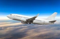 O avião do passageiro voa em um nível de voo contra um fundo das nuvens e de um céu azul Fotografia de Stock Royalty Free