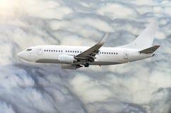 O avião do passageiro voa na altura de ganho do céu acima das nuvens Foto de Stock